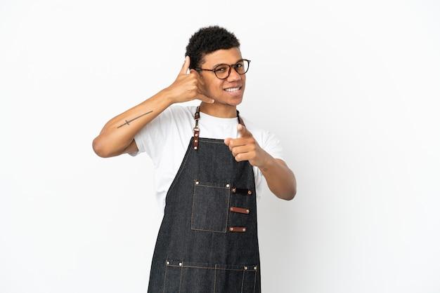 Restaurant afro-amerikaanse ober man geïsoleerd op een witte achtergrond telefoon gebaar maken en naar voren wijzen