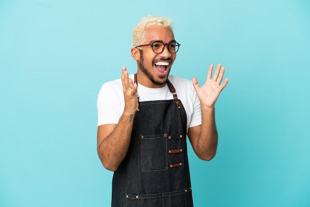 Restaurant colombiaanse ober man geïsoleerd op blauwe achtergrond met verrassing gezichtsuitdrukking