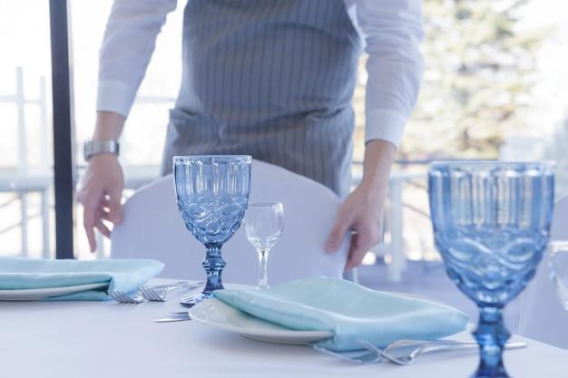 Restaurant de ober serveert een tafel voor een huwelijksfeest, beweegt een stoel