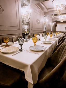 Restaurant eettafel met borden bestek geel en blauw glazen