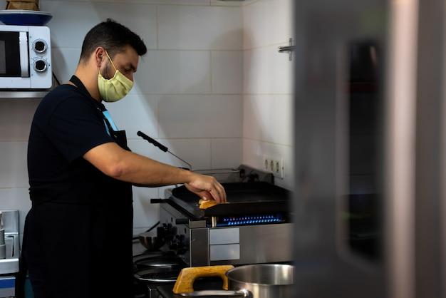 Restaurant en bar kok aan het werk in de keuken met een masker in het nieuwe normaal van de covid 19