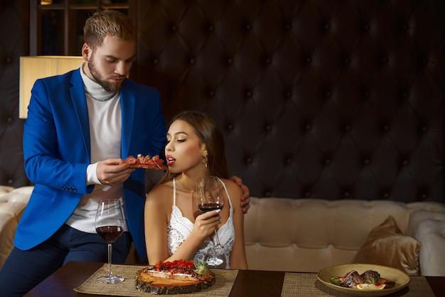 Restaurant en vakantieconcept - luxueus paar dat bij restaurant eet. het meisje eet uit de handen van een kerelbruschetta