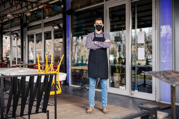 Restaurant gesloten vanwege epidemiologische coronavirussituatie. portret van een mannelijke ober in een geruite overhemd en schort met een beschermend gezichtsmasker staande voor een restaurant met zijn armen gekruist