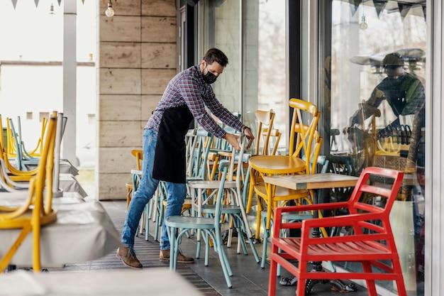 Restaurant gesloten wegens coronavirussituatie. ober in een geruit overhemd en schort met een beschermend gezichtsmasker verwijdert stoelen