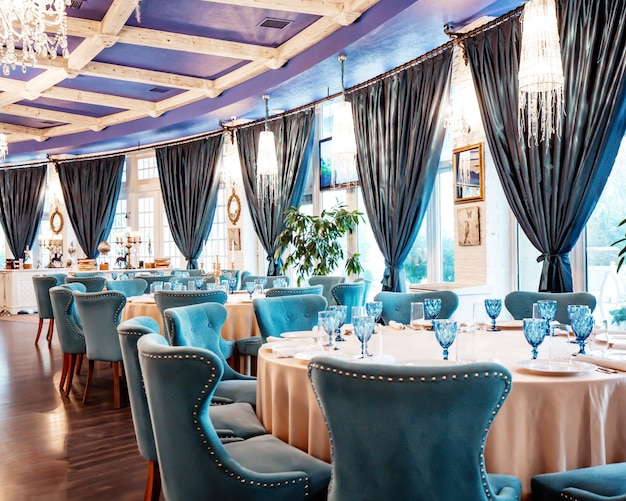 Restaurant hal met blauwe stoelen en blauwe glazen op tafel