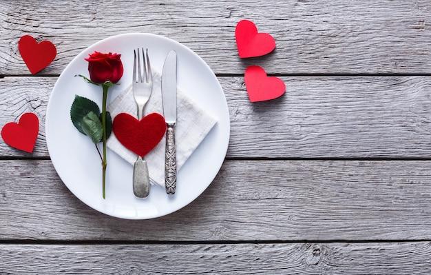 Restaurant houten tafel met hart en roos met bestek op plaat