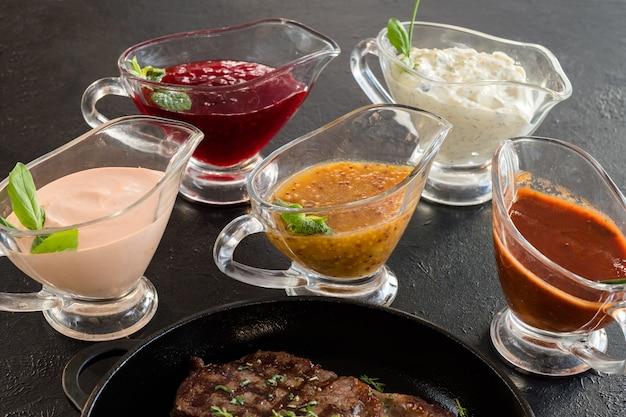 Restaurant menu. geroosterd vlees en saus op donkergrijs