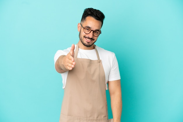 Restaurant ober blanke man geïsoleerd op blauwe achtergrond handen schudden voor het sluiten van een goede deal