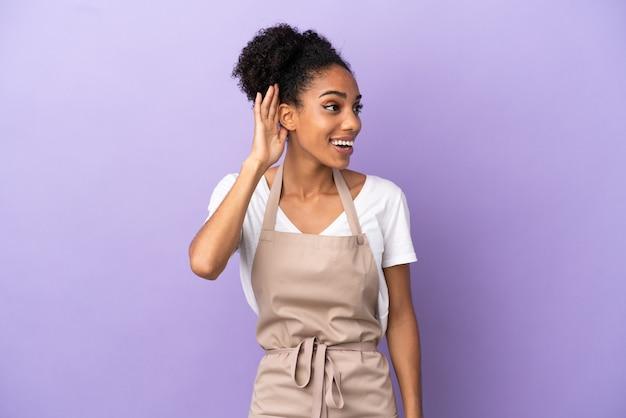 Restaurant ober latijnse vrouw geïsoleerd op paarse achtergrond luisteren naar iets door hand op het oor te leggen