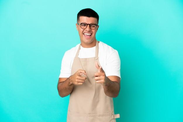 Restaurant ober man over geïsoleerde blauwe achtergrond die naar voren wijst en glimlacht