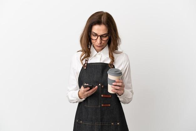 Restaurant van middelbare leeftijd ober vrouw geïsoleerd op een witte achtergrond met koffie om mee te nemen en een mobiel