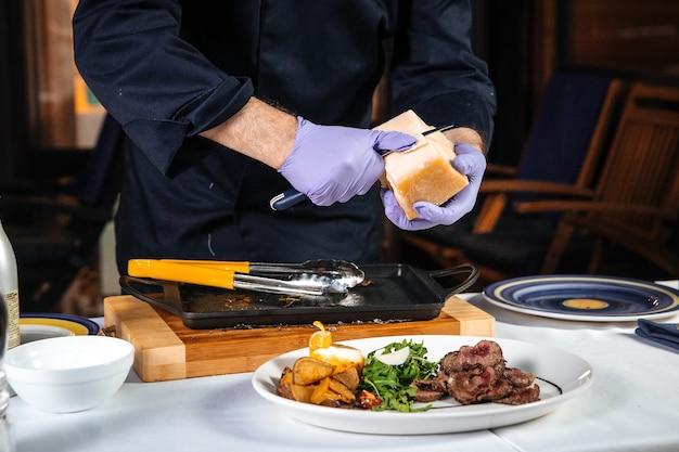 Restaurantchef-kok die schaafsel van parmezaanse kaas op de schotel met vlees en aardappelen schraapt
