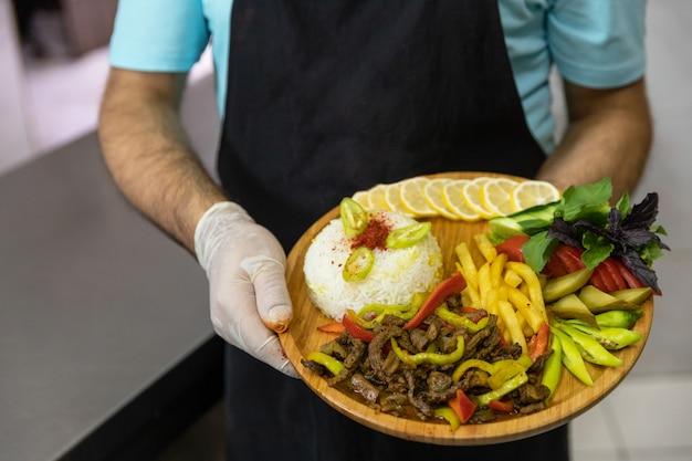 Restaurantchef-kok die smakelijke vleesmaaltijd met salade, groenten op de houten plaat houden