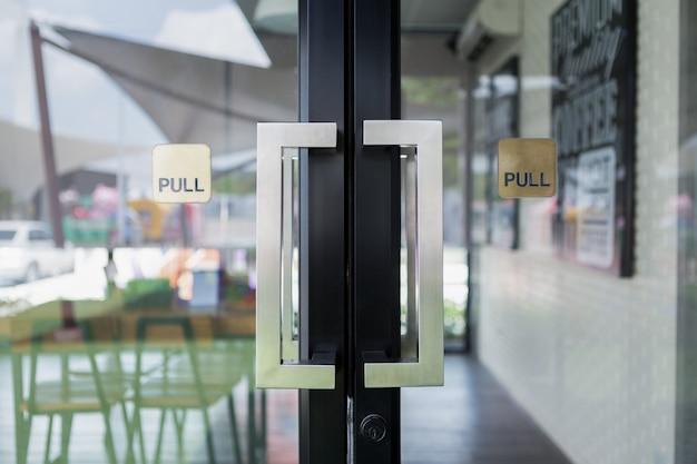 Restaurantdeurkruk op glazen deur met reflecterende galssschaduw