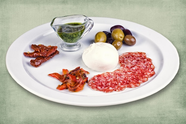 Restaurantgerecht bestaande uit vleeswaren, olijven, ei en saus