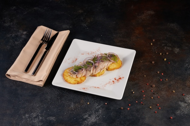 Restaurantgerecht - gebakken aardappelen met uienringen en haring