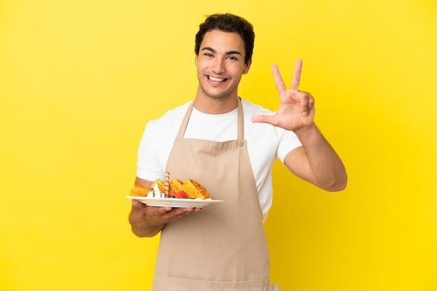 Restaurantkelner die wafels over geïsoleerde gele achtergrond gelukkig houdt en drie met vingers telt