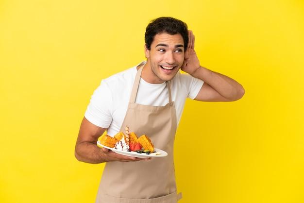 Restaurantkelner die wafels vasthoudt over een geïsoleerde gele achtergrond die naar iets luistert door de hand op het oor te leggen