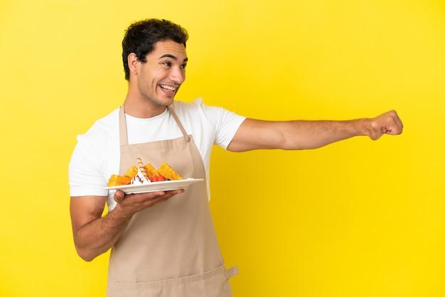 Restaurantkelner die wafels vasthoudt over geïsoleerde gele achtergrond en een duim omhoog gebaar geeft