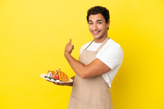 Restaurantkelner met wafels over geïsoleerde gele achtergrond die terug wijst