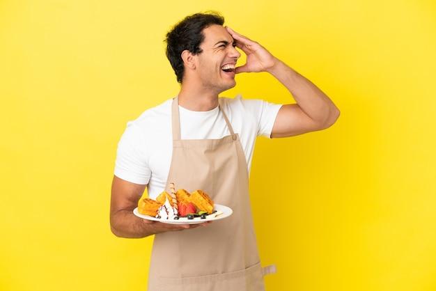 Restaurantkelner met wafels over geïsoleerde gele achtergrond die veel lacht