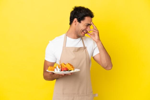 Restaurantkelner met wafels over geïsoleerde gele achtergrond lachend