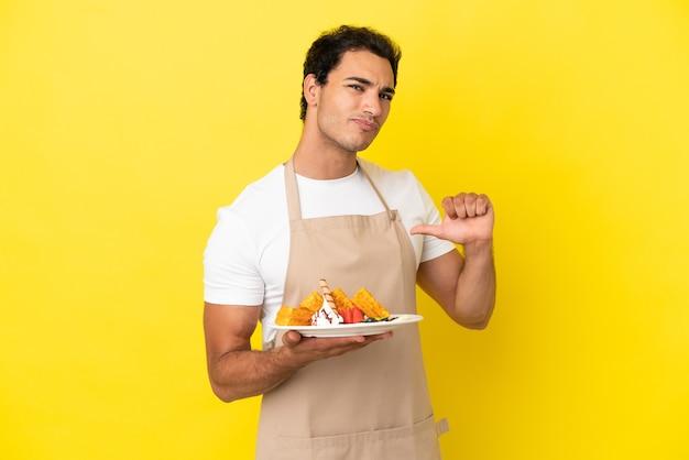 Restaurantkelner met wafels over geïsoleerde gele achtergrond, trots en zelfvoldaan
