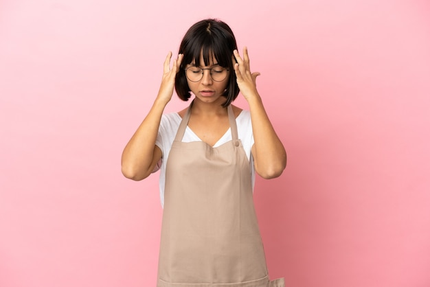 Restaurantkelner over geïsoleerde roze achtergrond met hoofdpijn