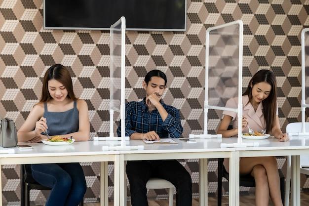 Restaurantklanten hebben een stoel met tafelafscherming voor sociale afstand