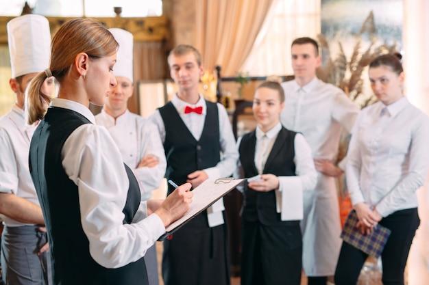 Restaurantmanager en zijn personeel in keuken. interactie met de chef-kok in de commerciële keuken.