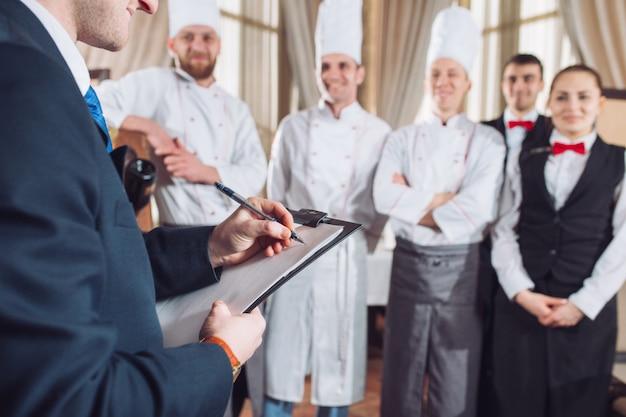 Restaurantmanager en zijn personeel in keuken. interactie tot chef-kok in commerciële keuken.