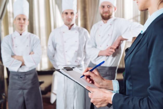 Restaurantmanager en zijn personeel in keuken.