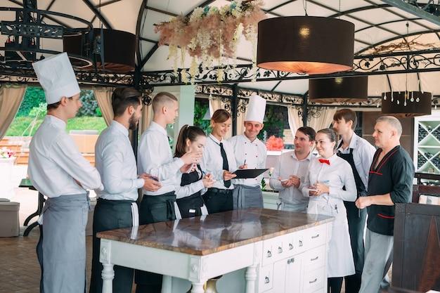 Restaurantmanager en zijn personeel op terras. interactie met chef-kok in restaurant.