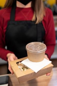 Restaurantmedewerker die de bestelling overhandigt aan een klant