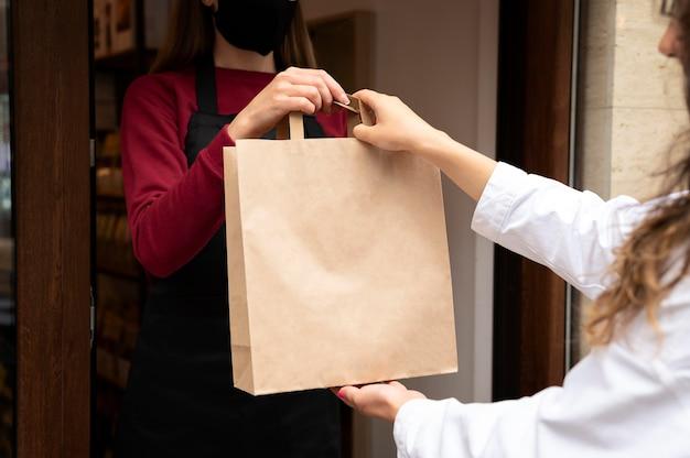 Restaurantmedewerker die de bestelling overhandigt aan een klant Premium Foto