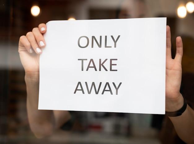Restaurantmedewerker die een afhaalbord voor het restaurant zet