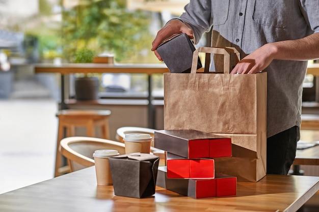Restaurantmedewerker die voedseldozen inpakt om mee te nemen. stelletje lege wegwerpcontainers voor afhaalmaaltijden gestapeld met papieren zakken en dozen met kopieerruimte voor het merklogo.
