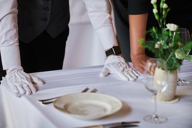 Restaurantpersoneel bereidt de fijne eettafel voor.