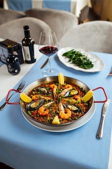 Restauranttafel geserveerd met spaanse gerechten, zeevruchten paella en padron pepers