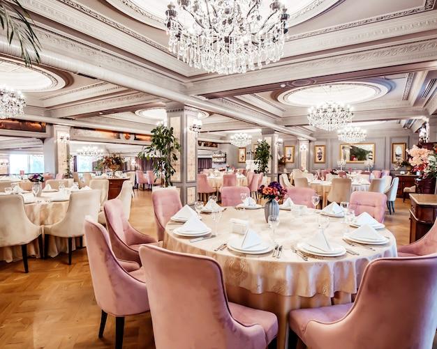 Restaurantzaal met ronde en vierkante tafels, stoelen en planten