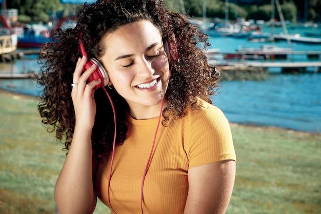 Retrato de una mujer rizada que escucha msica con auriculares sonriendo al aire libre.
