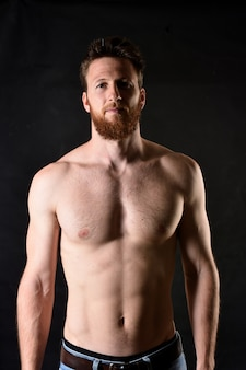 Retrato del hombre sin camisa y con el fondo negro.