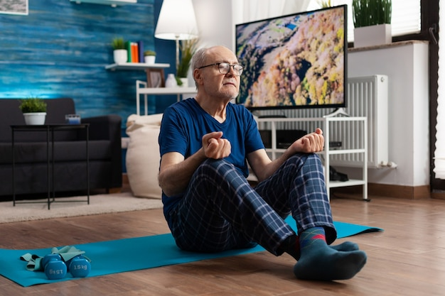 Retreat senior man zittend comfortabel in lotuspositie op yogamat met gesloten ogen pilates doen