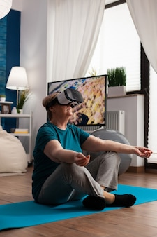 Retreat senior vrouw zittend op yogamat in lotuspositie in woonkamer met virtual reality