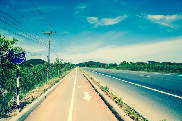 Retro asfaltweg in zonnige dag