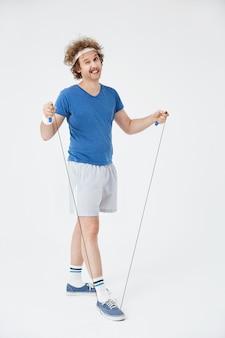 Retro atleet die met touwtjespringen uitoefenen die op wit wordt geïsoleerd