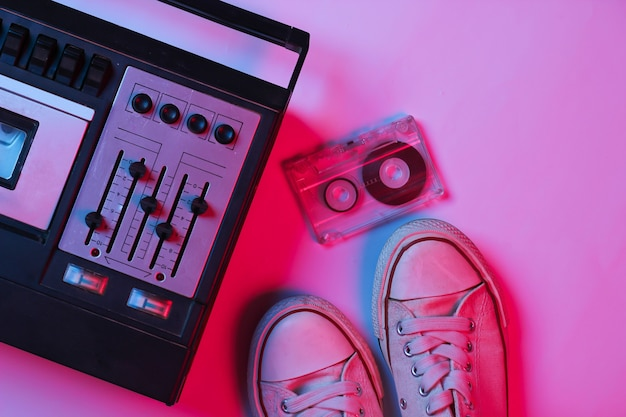 Retro audiobandrecorder, audiocassette, sneakers in roze blauw gradiënt neonlicht