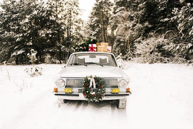 Retro auto met geschenken en kerstboom