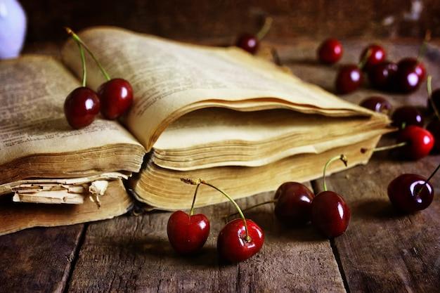 Retro boek over houten achtergrond en kersenbes