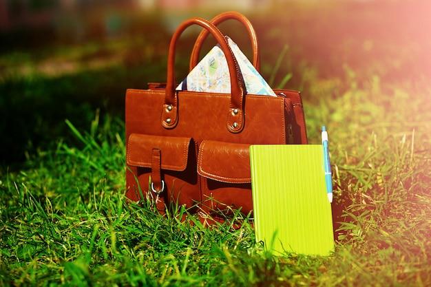 Retro bruine zak en het notitieboekje van het mensenleer in helder kleurrijk de zomergras in het park